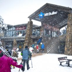 Snow falling as skiers stroll through the Village ready for a great day on the slopes.